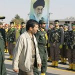 Iranian President Mahmoud Ahmadinejad (2nd L) and Revolutionary Guards' commander Yahya Rahim Safavi (L) review paramilitary volunteers from the Islamic Basij militia during a ceremony held at the mausoleum of the late revolutionary founder Ayatollah Khomeini just outside Tehran, 26 November 2006. Ahmadinejad called for the peoples of the Middle East and Afghanistan to join forces in driving out foreign occupiers. Tehran had repeatedly called for the withdrawal of US forces from its neighbours Iraq and Afghanistan. Portrait in the background shows Iran's supreme leader Ayatollah Ali Khamenei. AFP PHOTO/ATTA KENARE