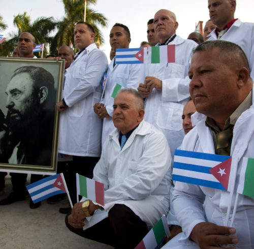 Several of the Cuban doctors and medical professionals that will depart for Italy to assist with the pandemic in the country pose for the media with a photo of Fidel Castro and flags of Italy and Cuba, in Havana, Cuba, Saturday, March 21, 2020. (AP Photo/Ismael Francisco)